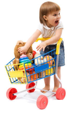 Little cute girl playing with toy shopping cart photo