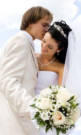 花嫁と花婿、青空をバックにキス