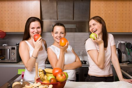 Three happy girls eating fruits. Healthy lifestyle concept photo