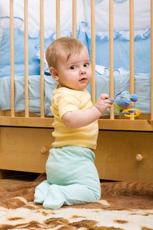 Cute little boy playing with toy near his crib photo