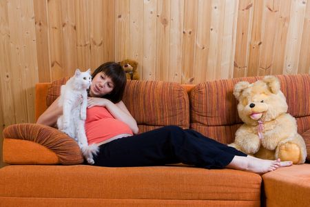 Happy pregnant young woman with cat sitting on the sofa photo