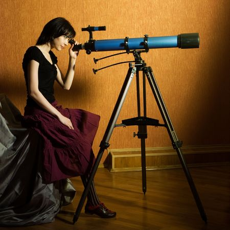 observatory: Young beautiful girl sitting on the bed looking to the telescope Stock Photo