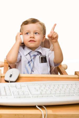 ni�os hablando: Un ni�o sentado en la mesa de trabajo con la computadora y hablando por tel�fono celular Foto de archivo
