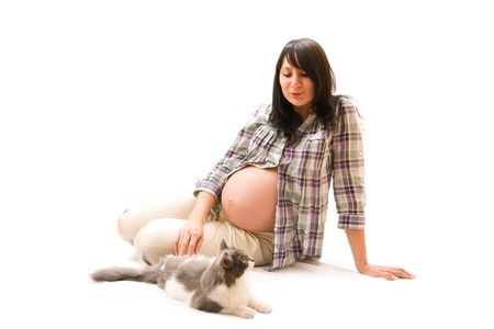 Young beautiful pregnant woman playing with her cat photo