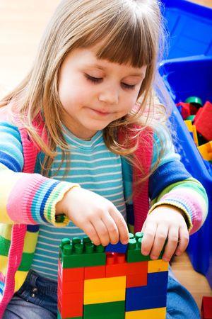 Ni�a sentada en el piso y jugar con los coloridos bloques Foto de archivo - 6622374