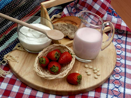 whig: milk, sour cream and strawberries on the wooden plate with towels Stock Photo
