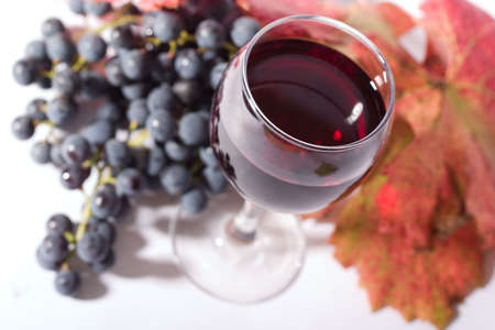 focal point: glass of red wine and black grapes. Low DOF, focal point is on wine Stock Photo