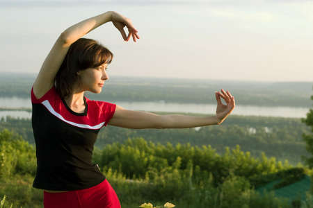 tai chi: young beautiful girl doing some exercises in the meadow