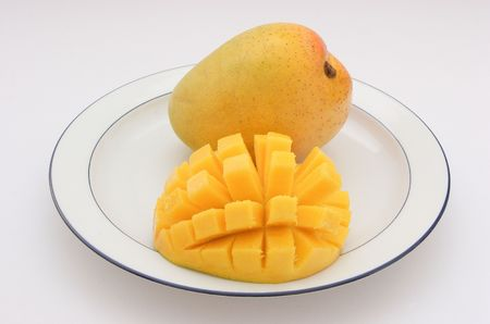 cubed: Mango - Sliced, cubed and whole on a plate