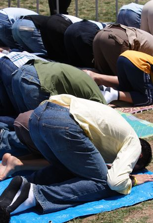 enclosures: A group of muslims praying outdoors