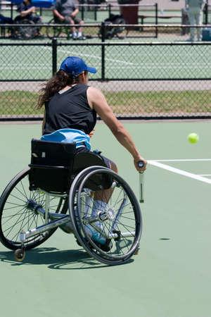 persona en silla de ruedas: Un atleta en silla de ruedas vinculados a la pista de tenis a punto de golpear una pelota  Foto de archivo