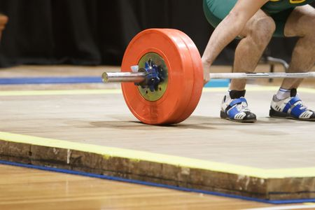 knees bent: A weightlifter about to lift