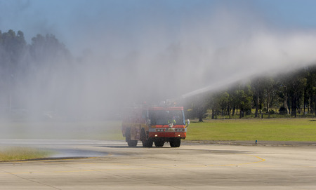 airfield: Fire engine with water spraying at an airfield Stock Photo