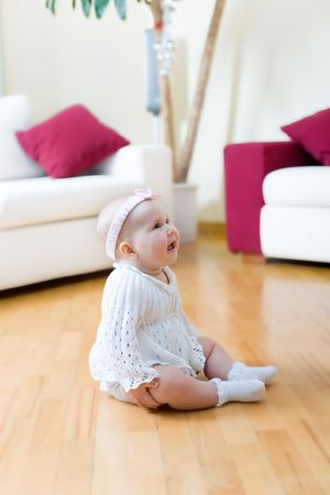 Happy eight month old baby girl seated on a hardwood floor in living room photo
