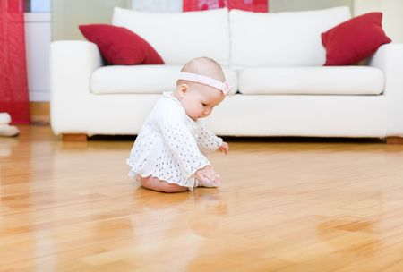 Happy baby girl tuching a hardwood floor