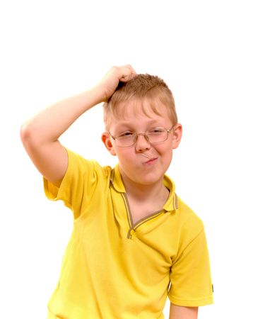 Boy scratches his head in puzzlement or confusion, as if pondering a deep question. Over white background. photo