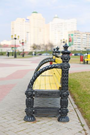 behind scenes: Park bench with city skyline behind. Focus on bench