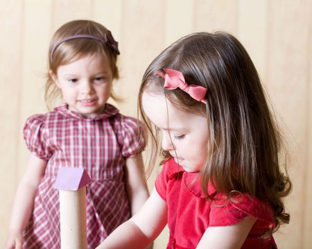 Portrait of two little girls building toy tower from wooden bricks at home Stock Photo - 3307931