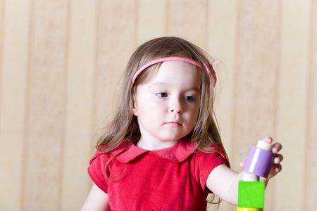 Portrait of a little girl building toy tower from wooden bricks at home Stock Photo - 3307930
