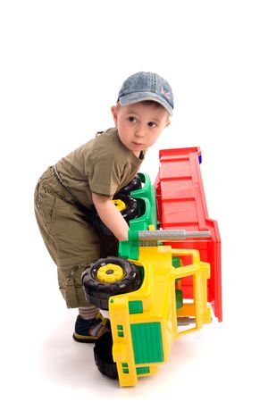 Little boys play with toy truck over white background with light shadows. Boy turn over the car Stock Photo - 3307927