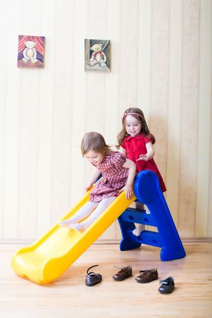 Two adorable girls having fun atop playground slide at living room Stock Photo