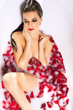 Attractive girl enjoys a bath with milk and rose petals  Spa treatments for skin rejuvenation photo
