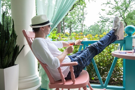 Man in a white hat and with glass of wine resting on the summer terrace photo