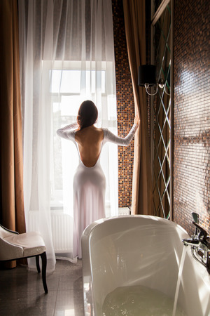 Attractive woman looking at window and preparing to take a bath photo