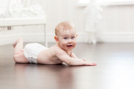 bebe gateando: Feliz niña de siete meses de rastreo en un piso de madera en la sala de estar