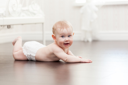 6 12: Happy seven month old baby girl crawling on a hardwood floor in living room