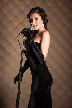 Beautiful brunette in retro style clothes with a microphone sings a song on stage photo