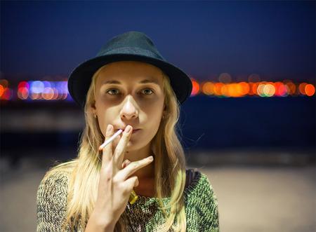 persona fumando: Chica joven en un sombrero de fumar un cigarrillo en la calle de Estambul Foto de archivo