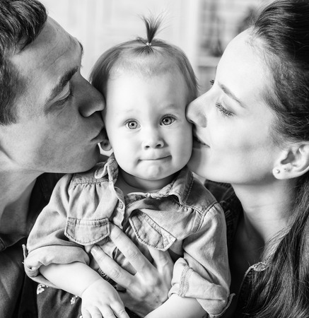 BW portrait of lovely family together at home. Mother and father kissing his year-old daughter photo