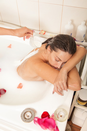 body milk: Attractive naked girl enjoys a bath with milk and rose petals.Spa treatment for skin nutrition and moisturizing skin renewal