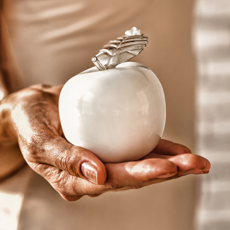 reaches: Old wrinkled hand reaches the apple of youth. The anti-aging concept. Stock Photo