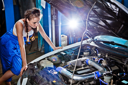 Female auto mechanic repairing a car, working on the transmission. photo