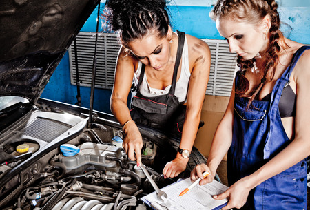 two car garage: Two female auto mechanic repairing a car, working on the transmission.