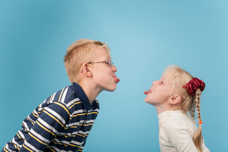 banter: Teenage boy and girl stick out tongues to each other Stock Photo