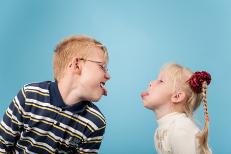 brother sister fight: Teenage boy and girl stick out tongues to each other Stock Photo