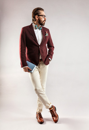 book jacket: Portrait of beautiful stylish young bearded man in a burgundy jacket and bow tie with book in hand