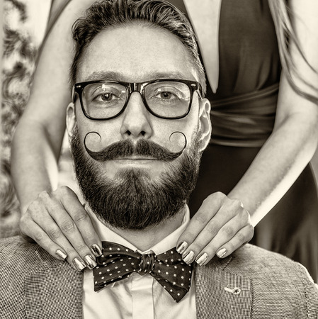 white beard: Woman with manicure straightens a bow tie to old-fashioned man in glasses with a beard and curled mustache. Photo toned in sepia, stylized retro shoot.