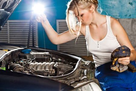Girl checks the oil level with dipstick in their own broken car photo
