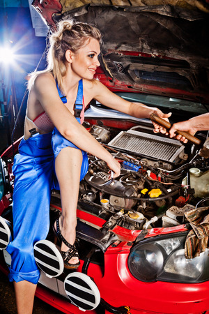 Man gives girl a tool to repair a car, working on the transmission. photo