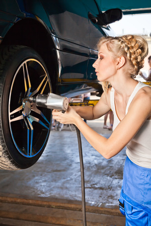 replaces: Female technician replaces the wheel of the vehicle in service.