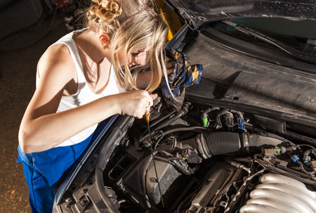 checks: Girl checks the oil level with dipstick in their own broken car