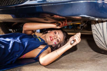 garage automobile: Femme technicien vérifie la suspension de la voiture de service.