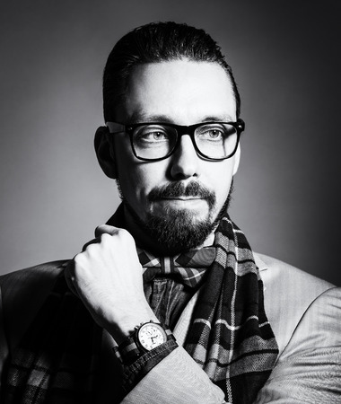 checkered scarf: Fashionable handsome stylish bearded man with glasses and in a checkered scarf and bow tie. Stock Photo