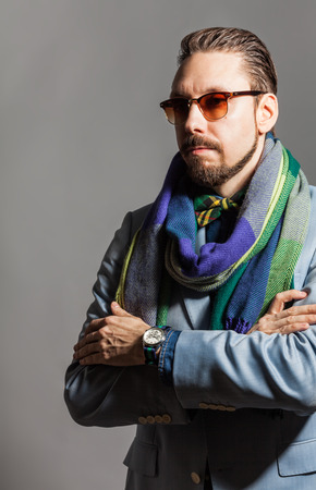 checkered scarf: Fashionable handsome stylish bearded man with sunglasses and in a checkered scarf and bow tie.