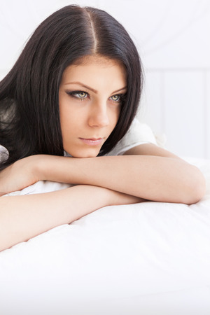 reflects: Sad young girl thoughtfully reflects lying on the bed