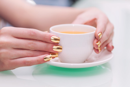 minx: Female hands with elegant gold manicure hold a cup of tea
